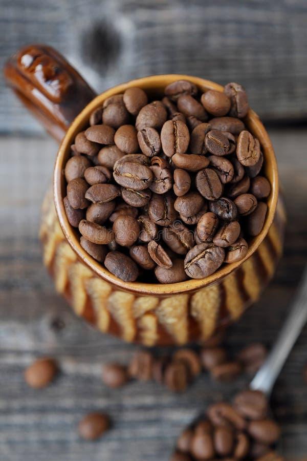 Grillade kaffebönor i en lera rånar arkivbilder