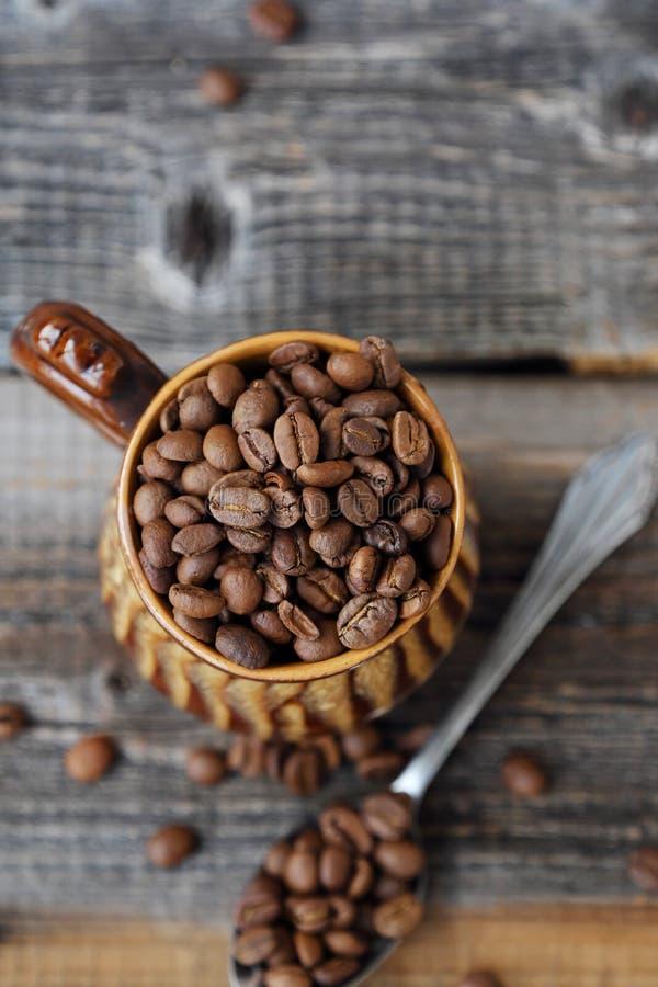 Grillade kaffebönor i en lera rånar royaltyfria foton
