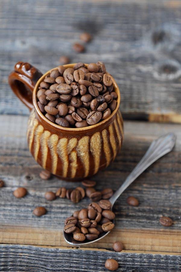 Grillade kaffebönor i en lera rånar royaltyfri foto