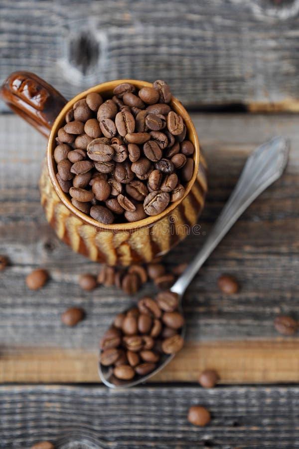 Grillade kaffebönor i en lera rånar royaltyfri bild