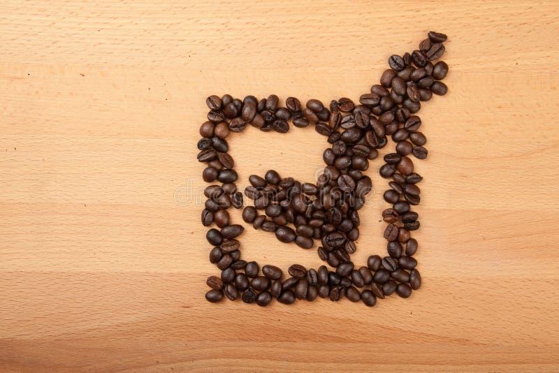 Grillade kaffebönor i kontrollfläck i ask formar royaltyfri fotografi