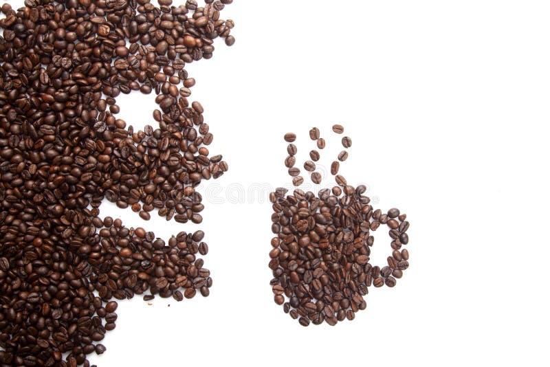 Grillade kaffebönor i man och kaffe rånar form fotografering för bildbyråer
