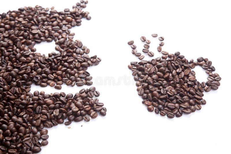 Grillade kaffebönor i man och kaffe rånar form arkivfoto