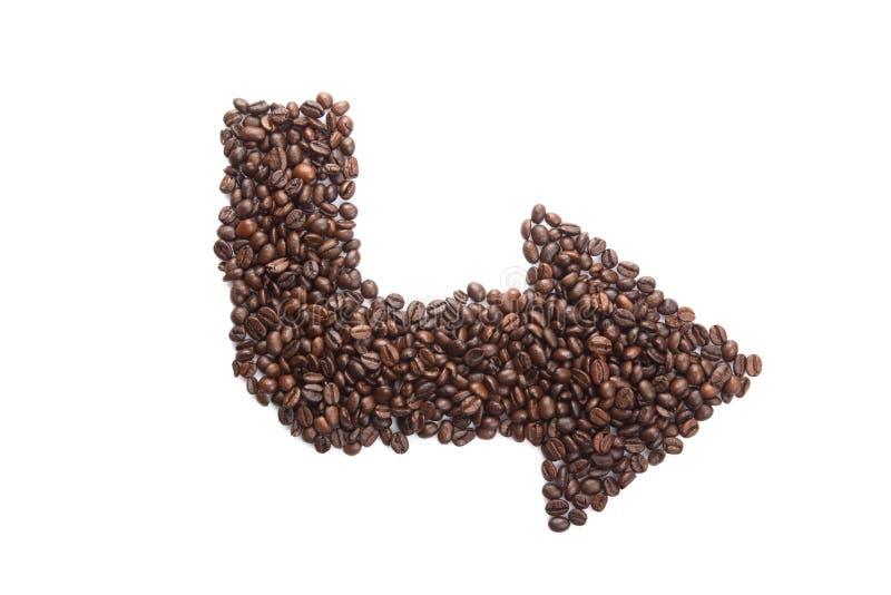 Grillade kaffebönor i pilform royaltyfria bilder