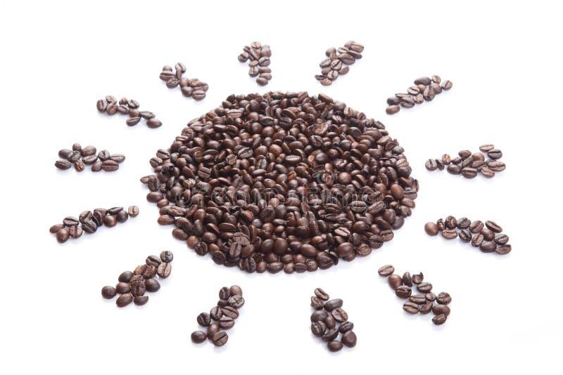 Grillade kaffebönor i solform arkivbilder