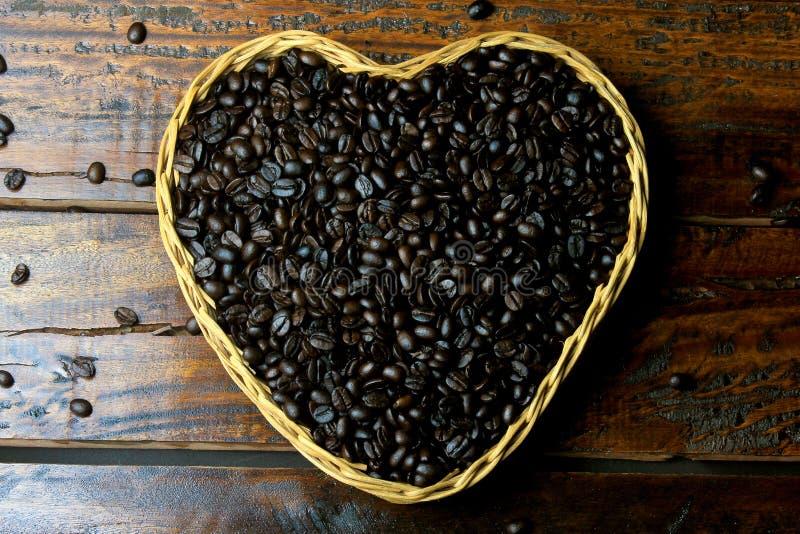 Grillade kaffebönor inom korg med hjärtaform på den lantliga trätabellen royaltyfri fotografi