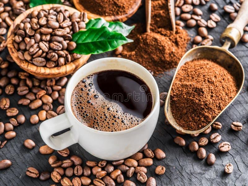 Grillade kaffebönor, jordkaffe och kopp kaffe på trä arkivbilder