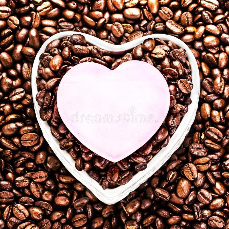 Grillade kaffebönor med det hjärta formade pappers- arket över kaffe b fotografering för bildbyråer