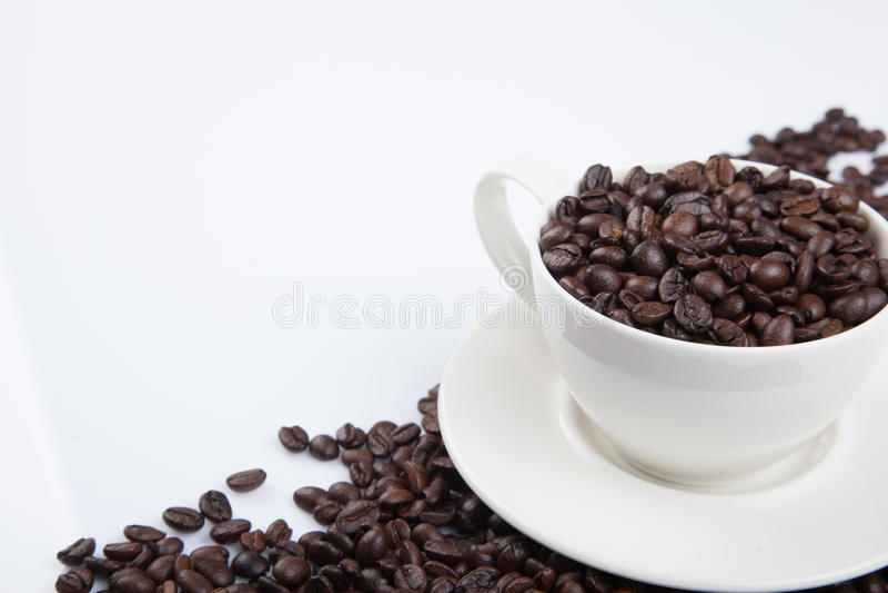 Grillade kaffebönor med en kopp arkivfoton