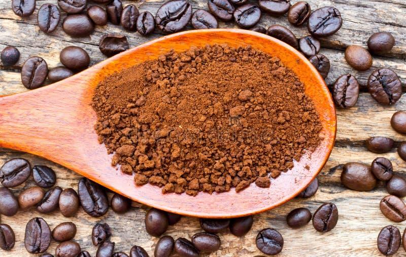 Grillade kaffebönor och jordkaffe i träsked royaltyfri bild