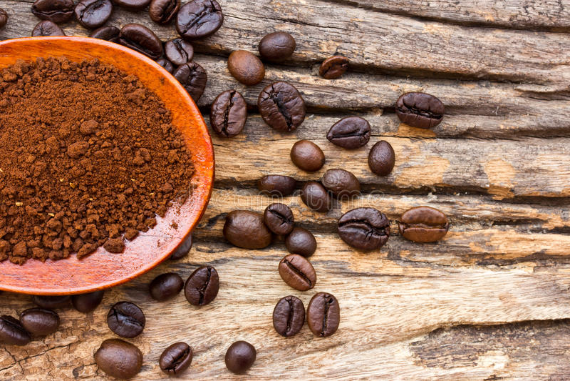 Grillade kaffebönor och jordkaffe i träsked arkivbilder
