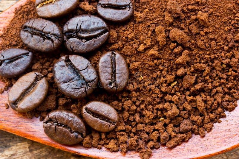 Grillade kaffebönor och jordkaffe i träsked arkivbild