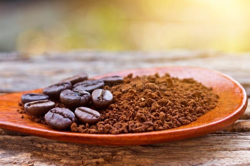 Grillade kaffebönor och jordkaffe i träsked på textur arkivfoton