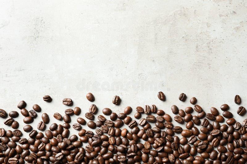 Grillade kaffebönor på grå bakgrund med utrymme royaltyfri foto