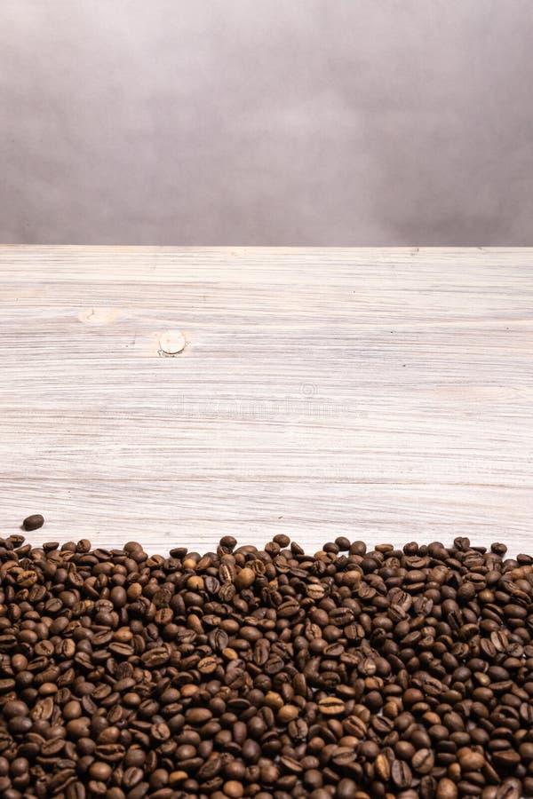 Grillade kaffeb?nor i massa p? en ljus tr?bakgrund shoppar den m?rka cofeen grillade kaf?t f?r kornanstrykningarom, naturlig coff royaltyfri fotografi