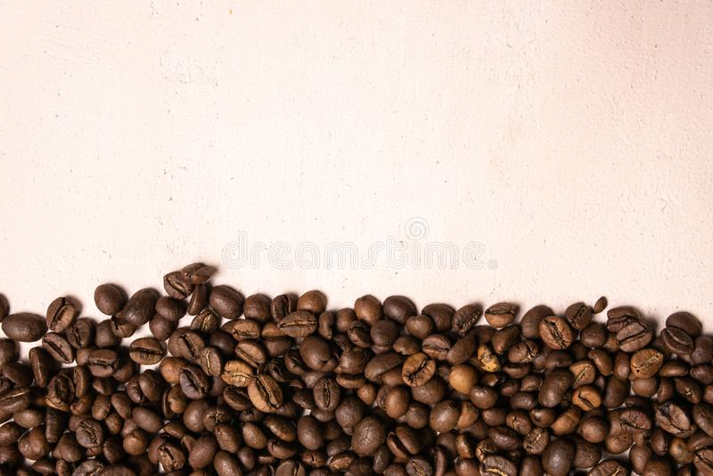 Grillade kaffeb?nor i massa p? ett ljust - rosa bakgrund shoppar den m?rka cofeen grillade kaf?t f?r kornanstrykningarom, naturli royaltyfri bild