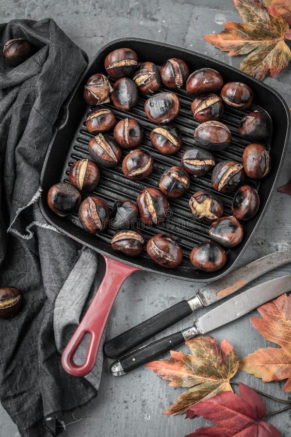 Grillade kastanjer tjänade som i kastanjebrun panna på en gammal tabell arkivfoto
