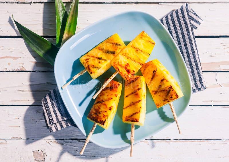 Grillade kilar av ananas på trästeknålar arkivfoton