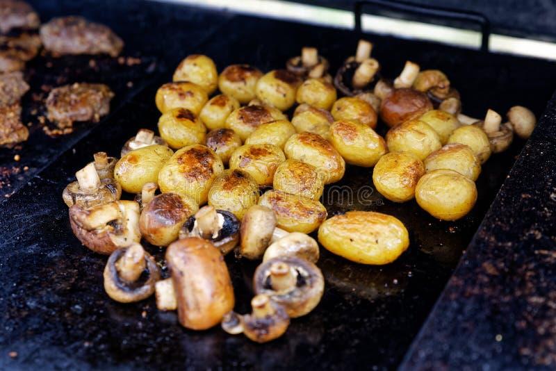 Grillade knappchampinjoner och hela potatisar på utomhus- galler royaltyfria foton