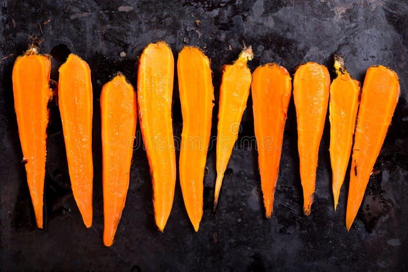 Grillade morötter på mörk bakgrund royaltyfri fotografi