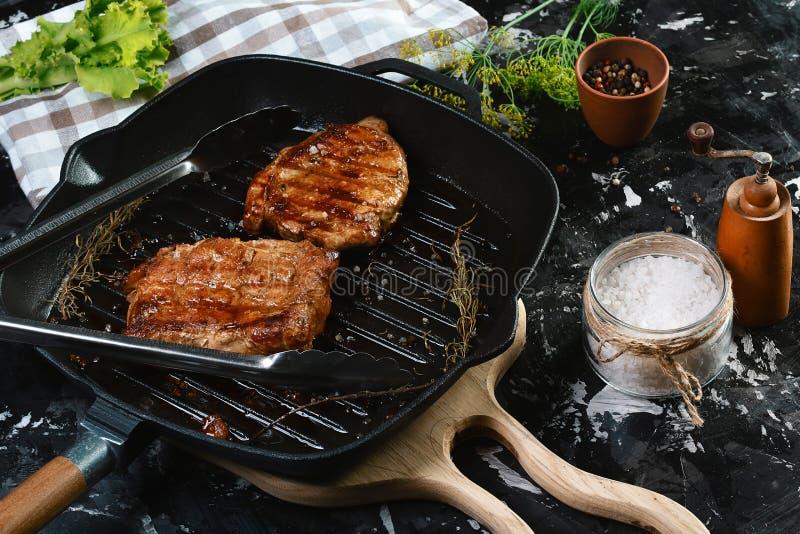 Grillade nötköttfilébiffar med örter och kryddor på mörk bakgrund olivgrön för olja för kök för kockbegreppsmat ny över hällande  arkivbilder