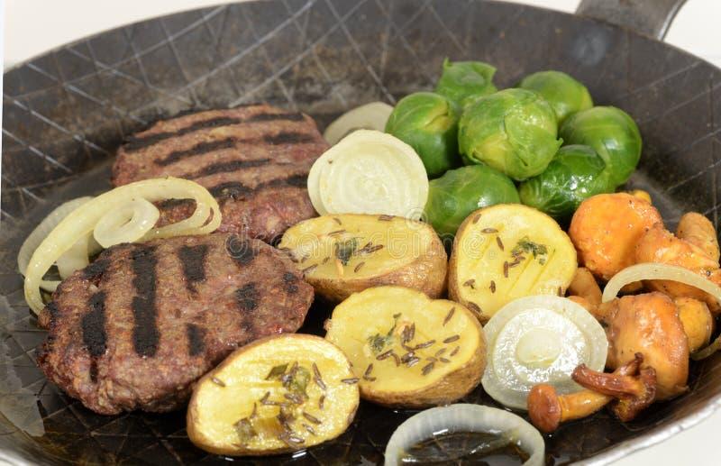 Grillade nötkötthamburgare med grönsaker royaltyfria foton