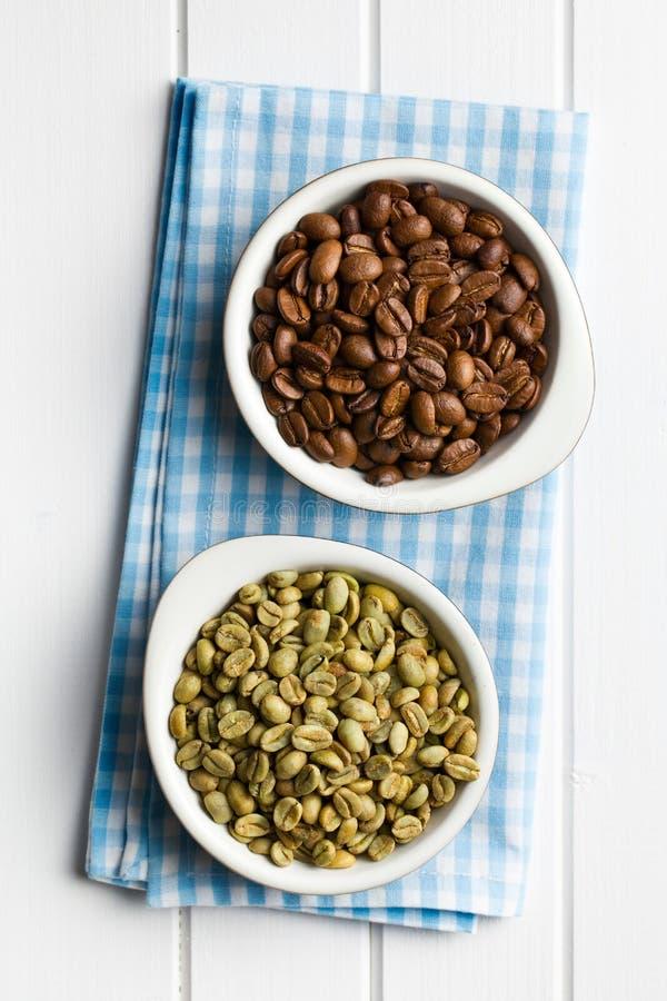 Grillade och unroasted kaffebönor i keramiska bunkar royaltyfri foto