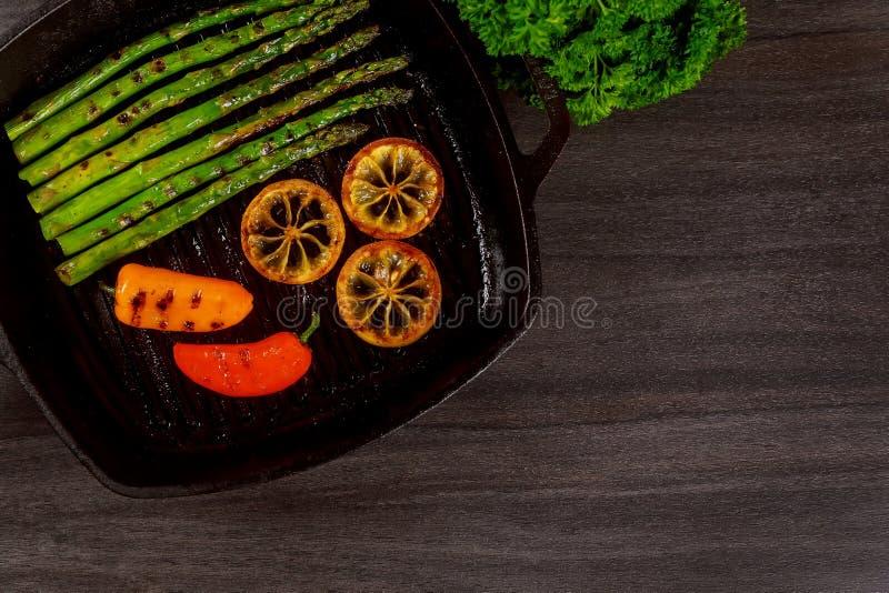 grillade organiska sparriers med citronen pepprar i en stekpanna royaltyfri bild