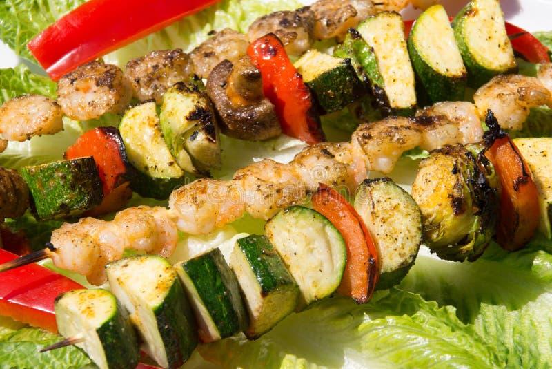 Grillade räka- och veggieskebabsteknålar arkivbilder