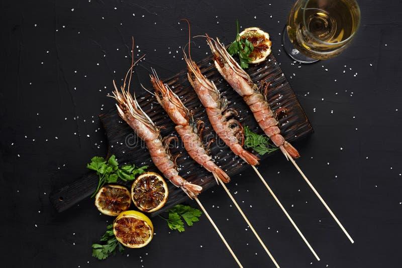grillade räkasteknålar Skaldjur skaldjur Räkaräkasteknålar med örter, vitlök och citronen på den svarta stenen royaltyfria foton