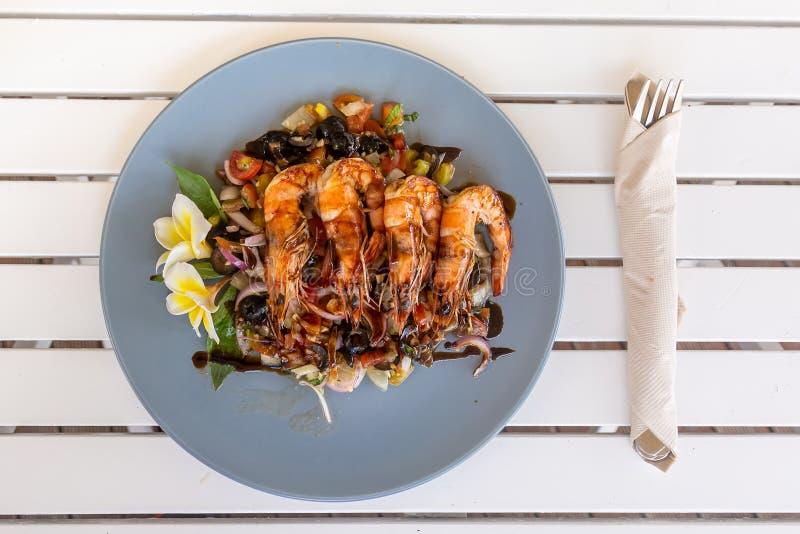 Grillade räkor eller räkor med stekte grönsaker på det ljust - blå platta Dekorerat med frangipaniblomman Gaffel och kniv på royaltyfri bild