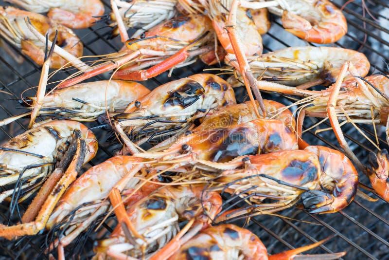 Grillade räkor på det flammande gallret som är havs- på gatafoods, marknadsför arkivfoto