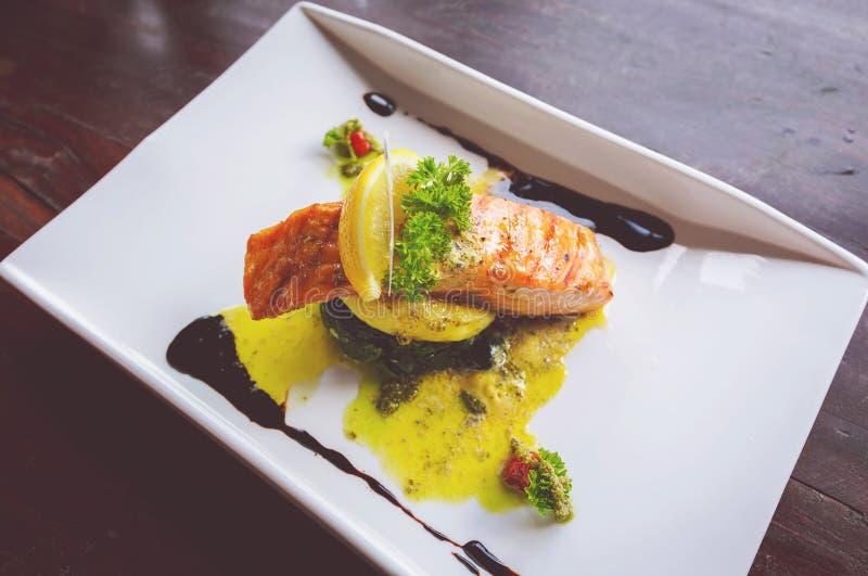 Grillade Salmon Steaks med limefrukt och bakade spenat royaltyfria bilder