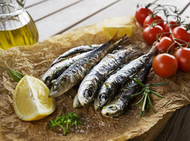 Grillade sardiner med örter och citronen arkivbilder