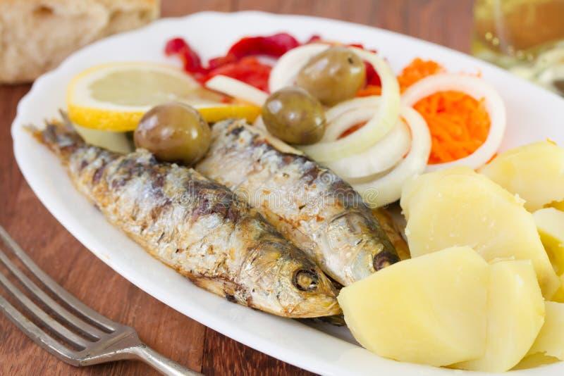 Grillade sardiner med den kokta potatisen arkivbild