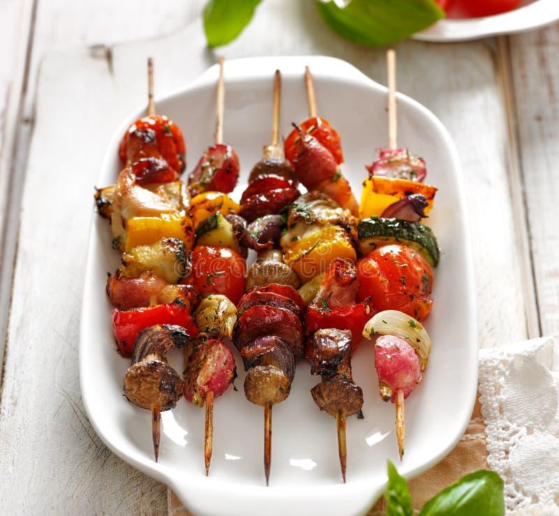 Grillade steknålar av grönsaker och kött i en örtmarinad på den vita plattan royaltyfri fotografi