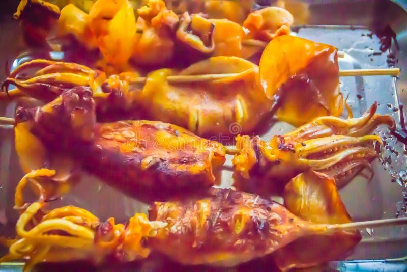 Grillade tioarmade bläckfiskar på kolugnen på natten festar Havs- barbecu arkivbild