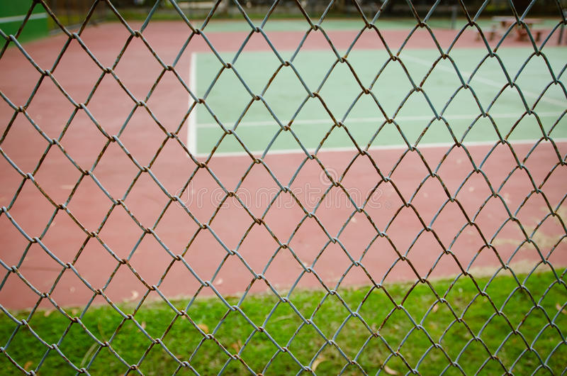 Grillage avec le court de tennis sur le fond photo libre de droits