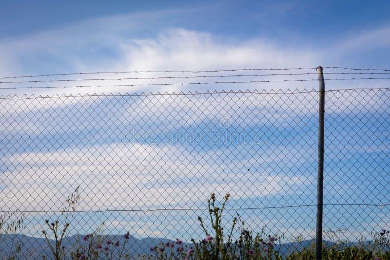 Grillage avec un ciel bleu avec des nuages images stock