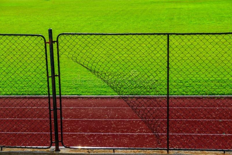 Grillage cassé de fer et voie de course sportive photographie stock