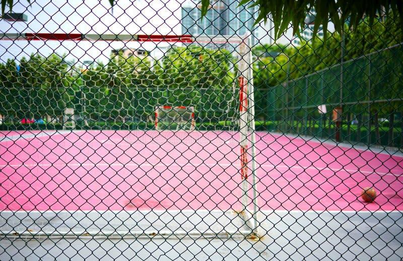 Grillage en métal ou acier vert de grillage avec le football de tache floue ou des sports roses de Futsal parquetant le fond image libre de droits