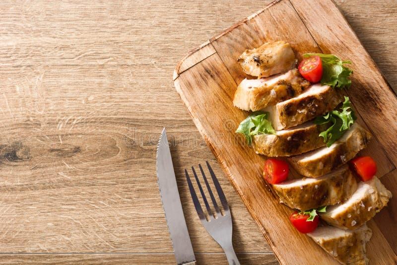 Grillat fegt bröst med grönsaker på trätabellen arkivfoto