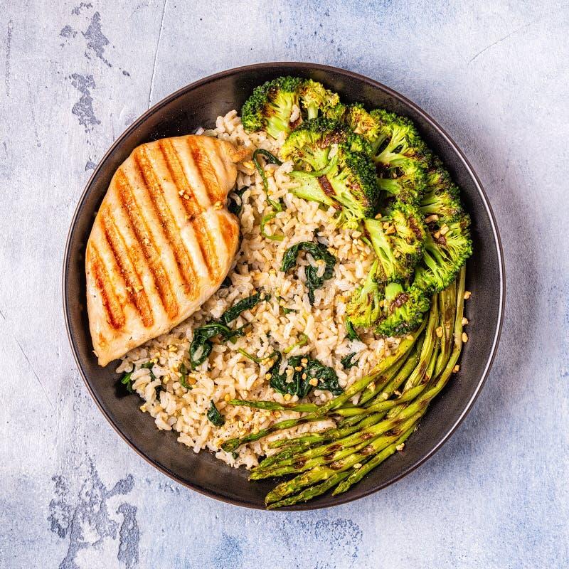 Grillat fegt bröst med råriers, spenat, broccoli som är aspar arkivfoto