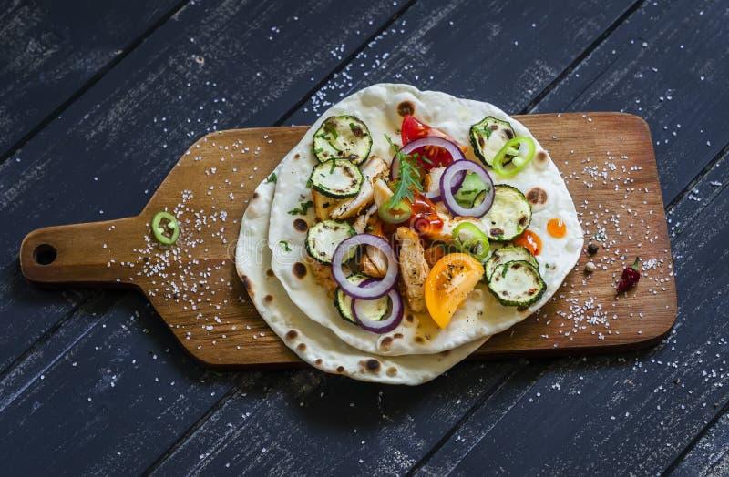 Grillat fegt bröst, nya grönsaker - tomater, gurkor, zucchini, lökar, peppar och hemlagad tortilla royaltyfri foto