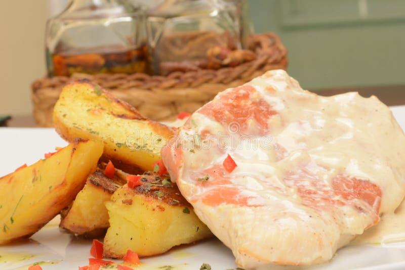 Grillat griskött med ost och bakade potatisar med kryddor arkivbilder