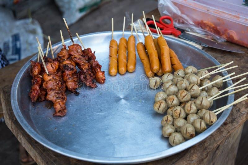 Grillat griskött och fega steknålar som är till salu i Thailand fotografering för bildbyråer