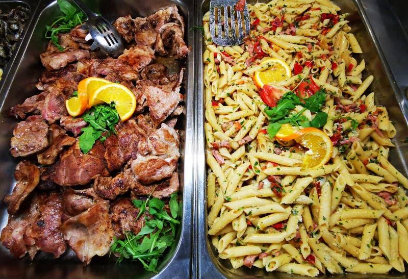 Grillat griskött och pasta som lagas mat med skinka royaltyfri bild
