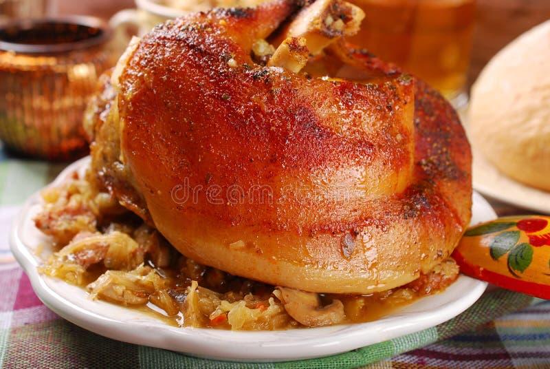 Grillat i ölgrisköttknoge med surkålen för matställe royaltyfria foton