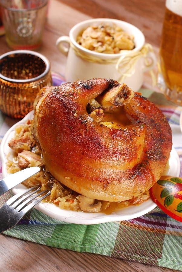 Grillat i ölgrisköttknoge med surkålen för matställe royaltyfri bild