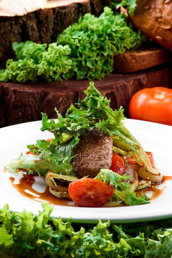 Grillat kött med grillade grönsaker och ny grönsallat i teriyakisås på den vita plattan på mörk träbakgrund royaltyfria foton